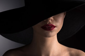young-woman-in-black-hat-with-red-lips-on-black-stock-photograph_csp47739598