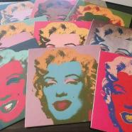 """A collection issued by """"After Warhol"""", of 9 wooden portraits in a box."""